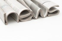 "The word ""News"" made of curtailed newspapers and lying on white background Слово «Новости», сделанное из свёрнутых газет и лежащих на белом фоне"