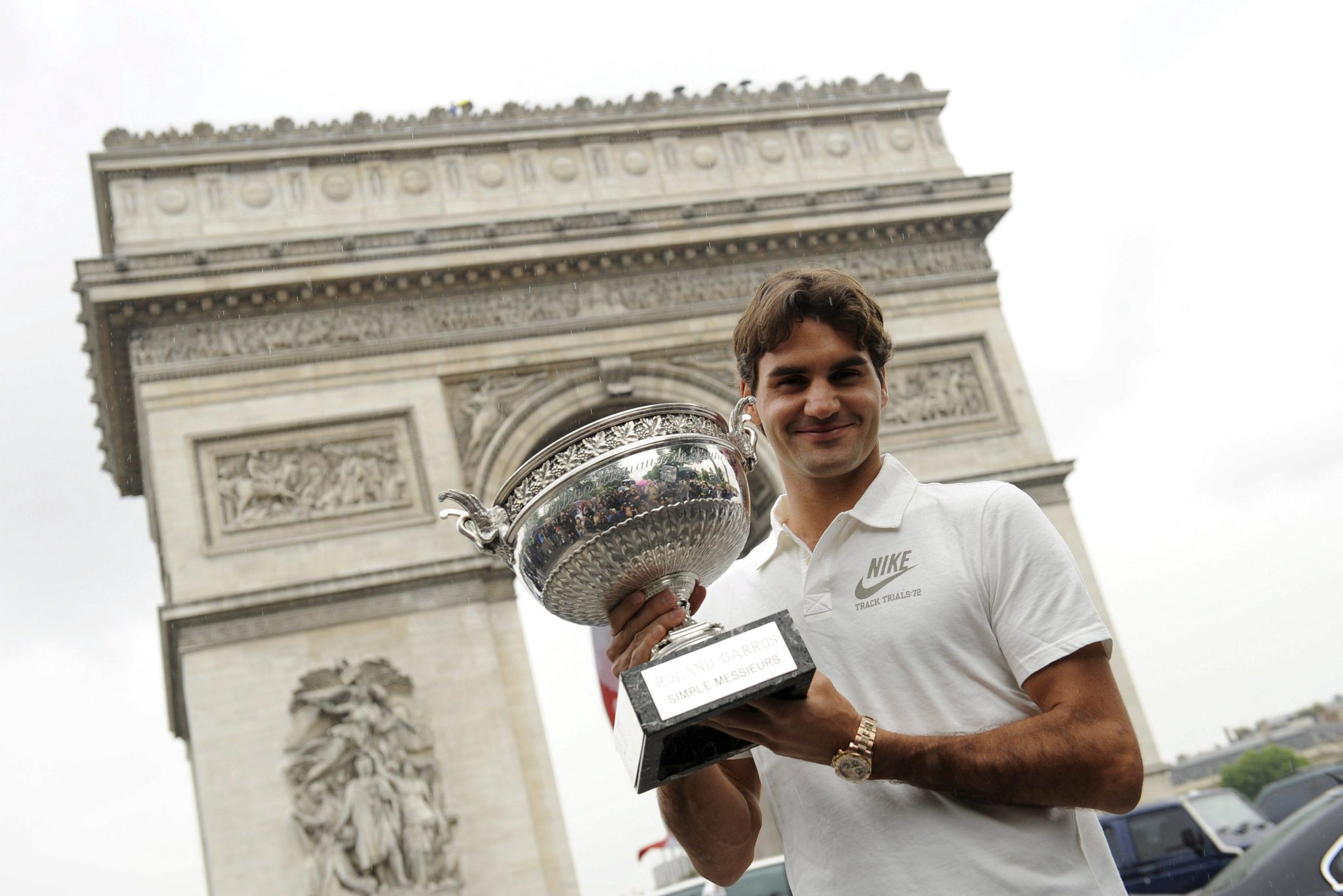 El tenista suizo Roger Federer muestra el trofeo mientras posa para los fotógrafos delante del Arco del Triunfo de París un día después de proclamarse campeón del Roland Garros, 8 de junio de 2009. EFE/Str