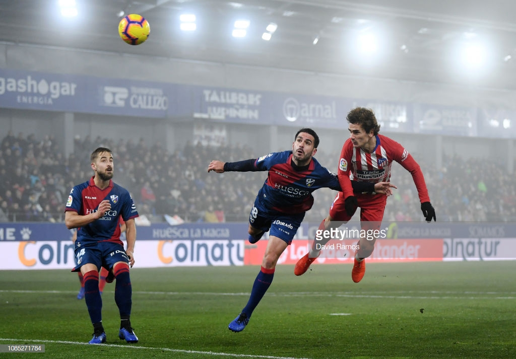 HUESCA, SPAIN - JANUARY 19: Antoine Griezmann of Atletico Madrid heads the ball under pressure from Pablo Insua of SD Huesca during the La Liga match between SD Huesca and Club Atletico de Madrid at Estadio El Alcoraz on January 19, 2019 in Huesca, Spain. (Photo by David Ramos/Getty Images)