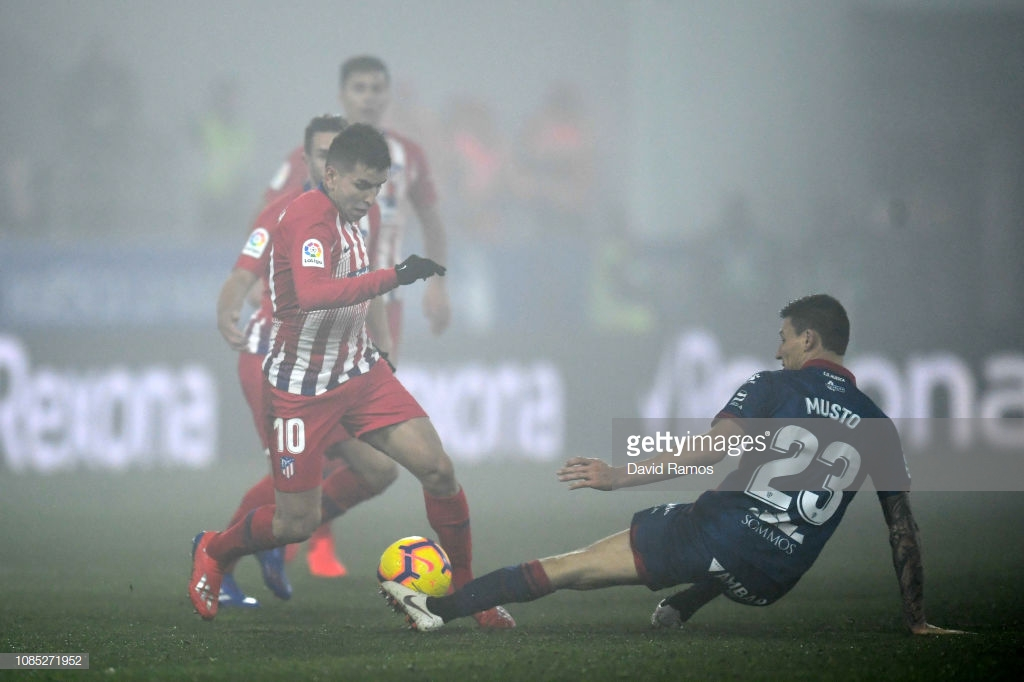 HUESCA, SPAIN - JANUARY 19: Angel Correa of Atletico Madrid battles for possession with Damian Musto of SD Huesca during the La Liga match between SD Huesca and Club Atletico de Madrid at Estadio El Alcoraz on January 19, 2019 in Huesca, Spain. (Photo by David Ramos/Getty Images)
